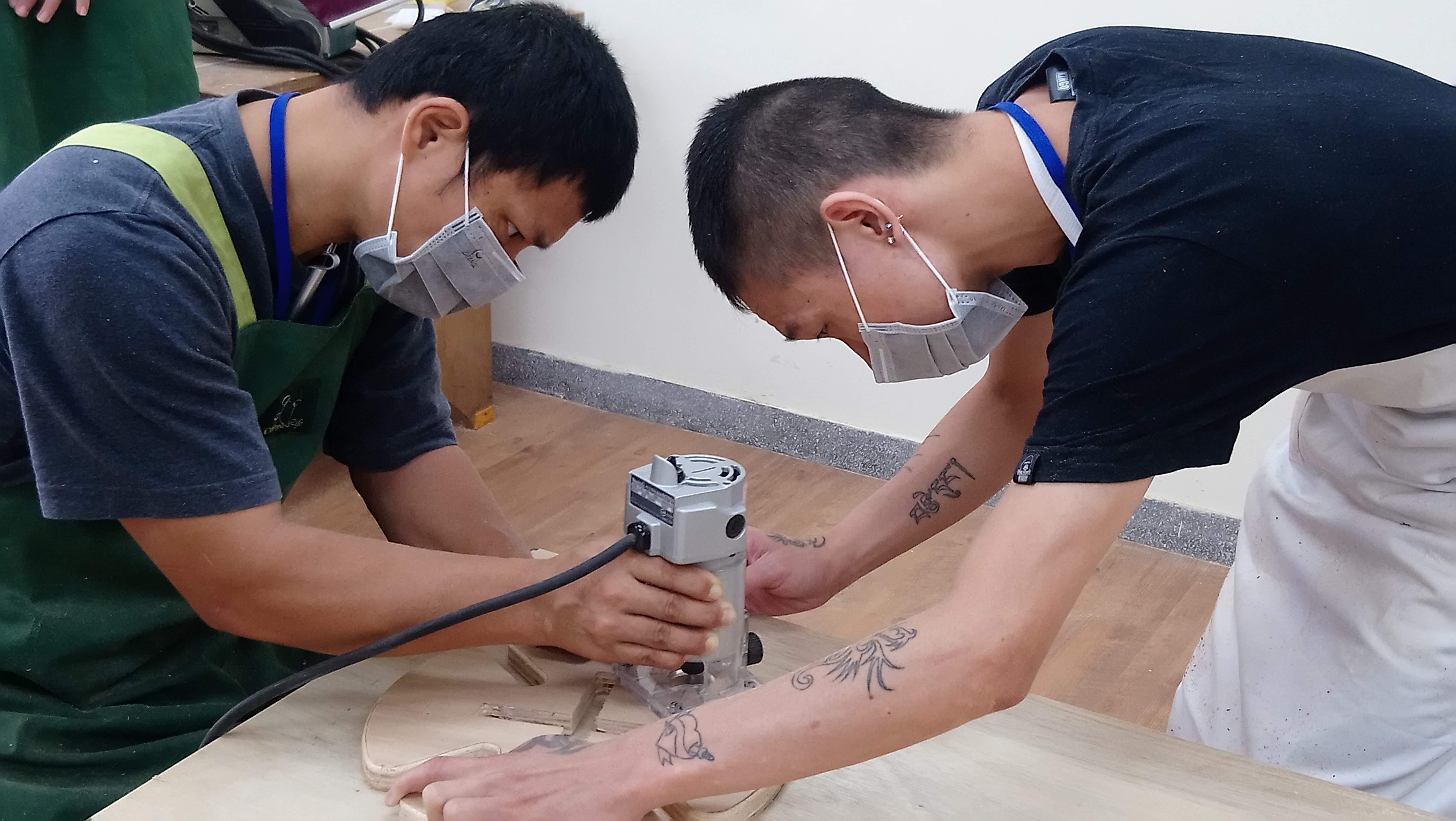 阿德(右)擔任小老師,指導同學操作打磨修邊機具。