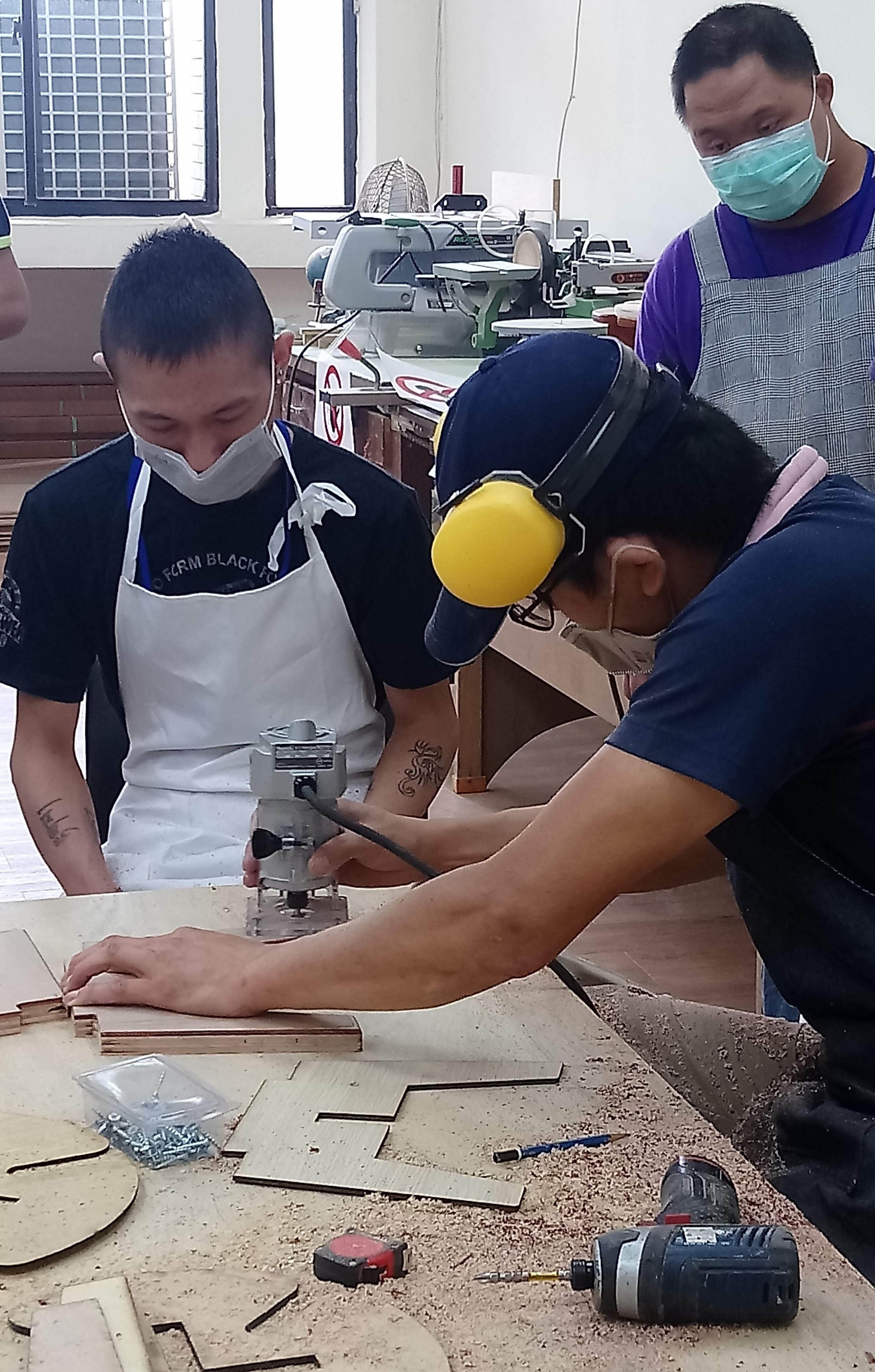 職訓師指導阿德(左)操作打磨機具。